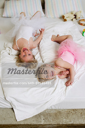 Portrait of two young sisters playing on bed Stock Photo - Premium Royalty-Free, Image code: 649-07585455