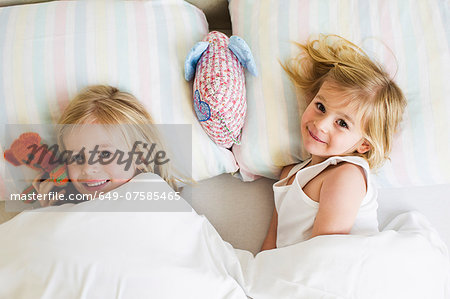 Portrait of two young sisters lying side by side in bed Stock Photo - Premium Royalty-Free, Image code: 649-07585465
