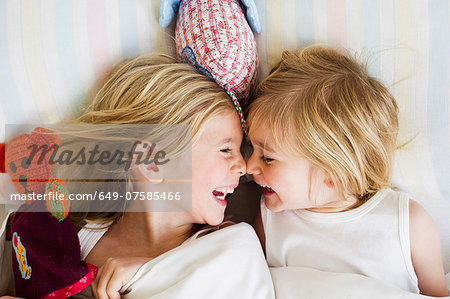 Portrait of two young sisters lying face to face in bed Stock Photo - Premium Royalty-Free, Image code: 649-07585466