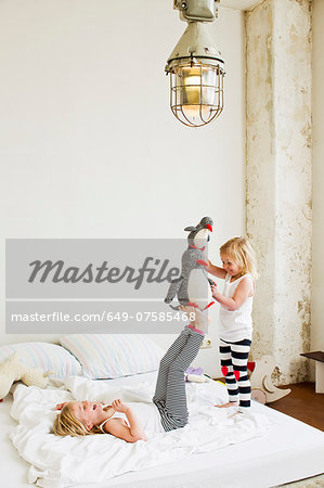 Young sisters playing with soft toy on the bed Stock Photo - Premium Royalty-Free, Image code: 649-07585468