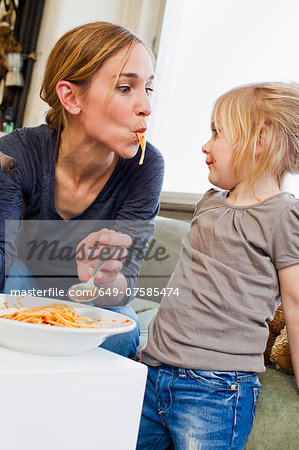 Mid adult mother eating spaghetti with her daughter Stock Photo - Premium Royalty-Free, Image code: 649-07585474