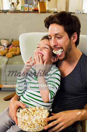 Father and young son with mouthfuls of popcorn Stock Photo - Premium Royalty-Free, Image code: 649-07585485