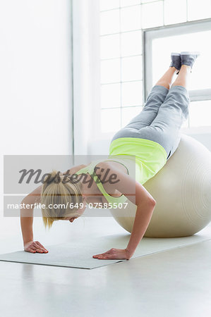 Young woman doing press up with exercise ball Stock Photo - Premium Royalty-Free, Image code: 649-07585507