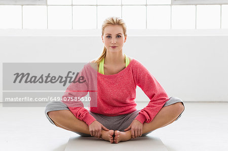 Young woman sitting on exercise mat Stock Photo - Premium Royalty-Free, Image code: 649-07585510