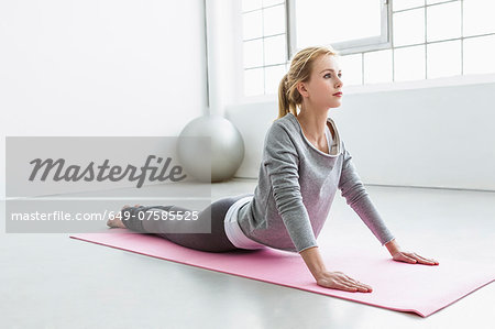 Young woman in yoga pose on yoga mat Stock Photo - Premium Royalty-Free, Image code: 649-07585525