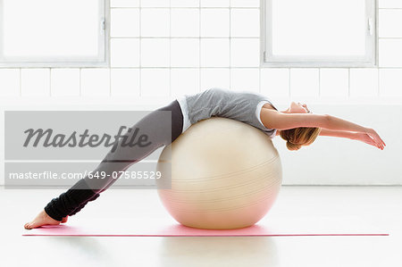 Young woman stretching on exercise ball Stock Photo - Premium Royalty-Free, Image code: 649-07585529