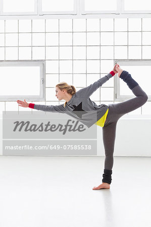 Young woman standing in yoga pose Stock Photo - Premium Royalty-Free, Image code: 649-07585538