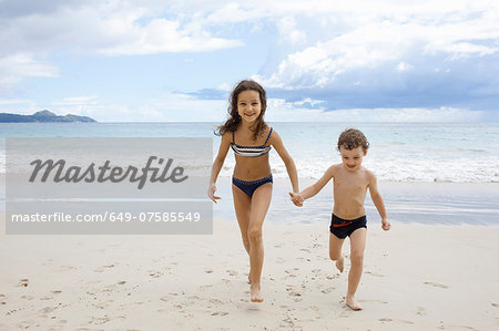 Brother and sister running on beach, holding hands Stock Photo - Premium Royalty-Free, Image code: 649-07585549