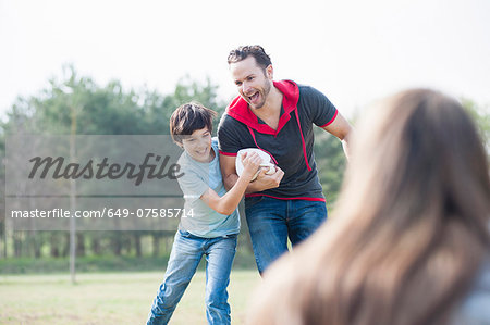 Father and son practicing rugby tackle in park Stock Photo - Premium Royalty-Free, Image code: 649-07585714