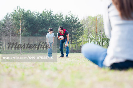 Boy practicing rugby with parents in park Stock Photo - Premium Royalty-Free, Image code: 649-07585715