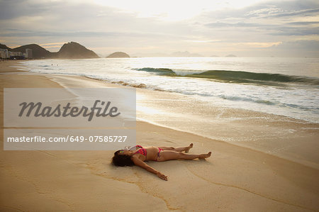 Mature woman sunbathing on Copacabana beach at sunset, Rio De Janeiro, Brazil Stock Photo - Premium Royalty-Free, Image code: 649-07585727