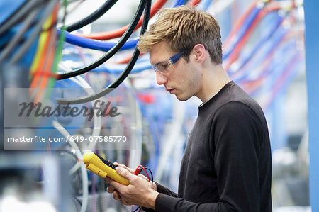 Mid adult male technician testing cables in engineering plant Stock Photo - Premium Royalty-Free, Image code: 649-07585770