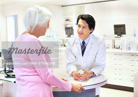 Male pharmacist advising customer on medication Stock Photo - Premium Royalty-Free, Image code: 649-07596148