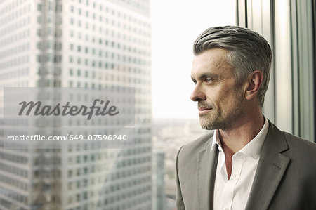 Portrait of mature businessman looking out of office window Stock Photo - Premium Royalty-Free, Image code: 649-07596240