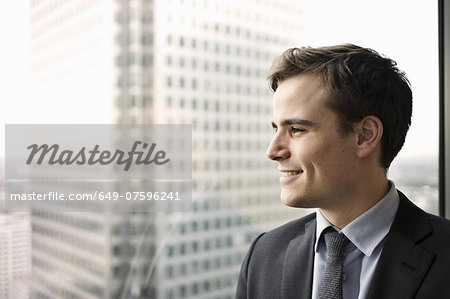 Portrait of young businessman looking out of office window Stock Photo - Premium Royalty-Free, Image code: 649-07596241