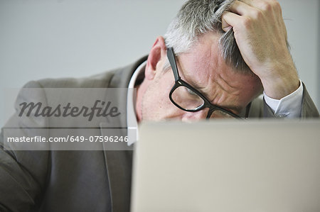 Stressed mature businessman in office Stock Photo - Premium Royalty-Free, Image code: 649-07596246