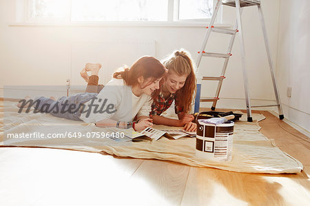 Two teenage sisters lying on floor looking at color swatches Stock Photo - Premium Royalty-Free, Image code: 649-07596480