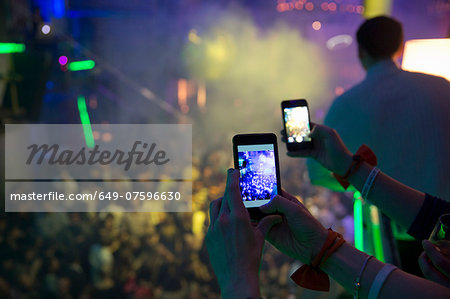Women taking photograph in nightclub with cellular phone Stock Photo - Premium Royalty-Free, Image code: 649-07596630