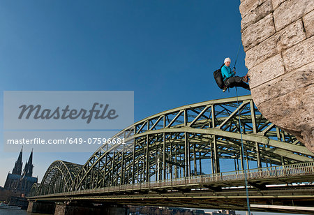 Female climber abseiling next to the Hohenzollern railway bridge, Cologne, Germany Stock Photo - Premium Royalty-Free, Image code: 649-07596681