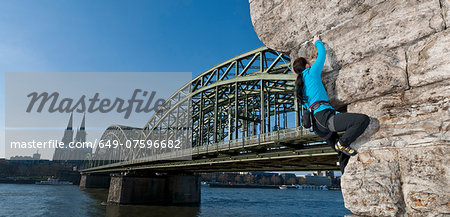 Female climber on man made wall next to the Hohenzollern railway bridge, Cologne, Germany Stock Photo - Premium Royalty-Free, Image code: 649-07596682