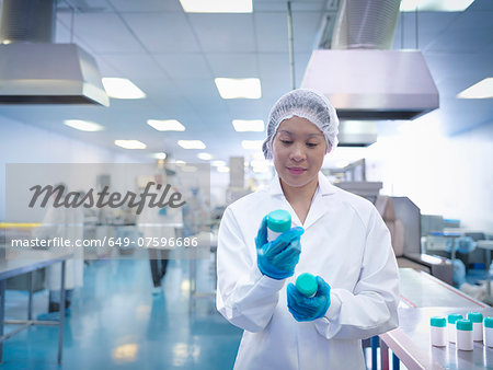 Worker inspecting packaging in pharmaceutical factory Stock Photo - Premium Royalty-Free, Image code: 649-07596686