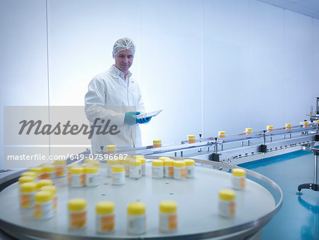 Worker inspecting packaging in pharmaceutical factory Stock Photo - Premium Royalty-Free, Image code: 649-07596687