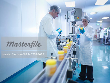 Workers inspecting packaging in pharmaceutical factory Stock Photo - Premium Royalty-Free, Image code: 649-07596688