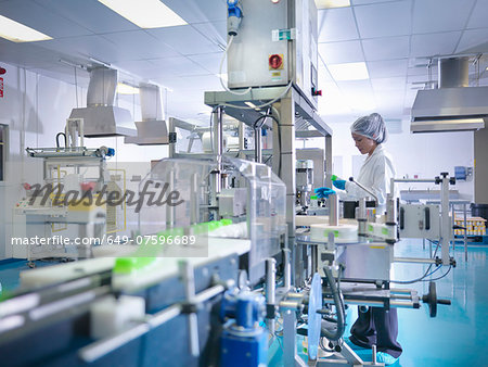 Worker inspecting products on production line in pharmaceutical factory Stock Photo - Premium Royalty-Free, Image code: 649-07596689