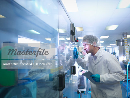 Worker inspecting tablets as they are put into packaging in pharmaceutical factory Stock Photo - Premium Royalty-Free, Image code: 649-07596692