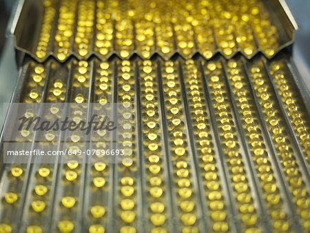 Rows of vitamin capsules in pharmaceutical factory Stock Photo - Premium Royalty-Free, Image code: 649-07596693