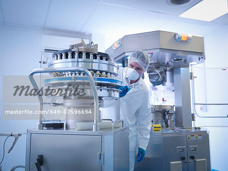 Engineer performing maintenance on tablet manufacturing machine in pharmaceutical factory Stock Photo - Premium Royalty-Free, Image code: 649-07596694