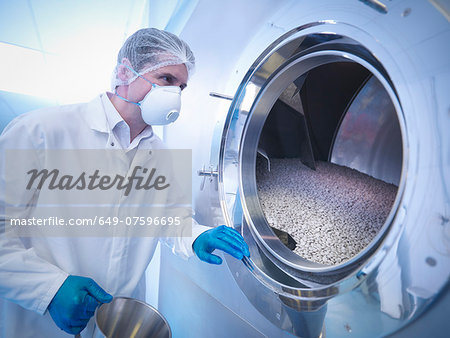 Worker using tablet coating machine in pharmaceutical factory Stock Photo - Premium Royalty-Free, Image code: 649-07596695