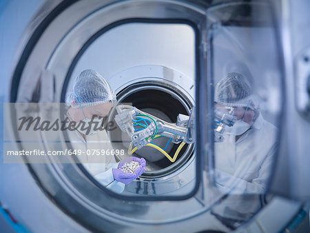 Worker inspects tablets in coating machine in pharmaceutical factory Stock Photo - Premium Royalty-Free, Image code: 649-07596698