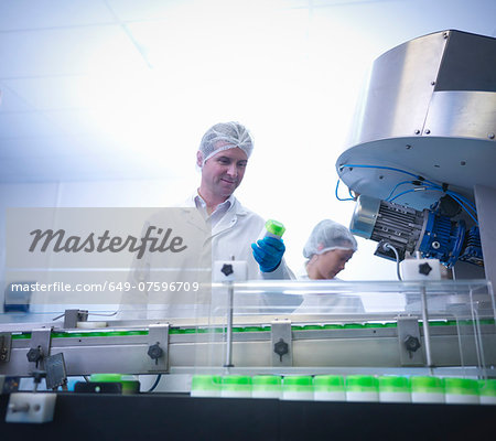 Workers inspecting products on production line in pharmaceutical factory Stock Photo - Premium Royalty-Free, Image code: 649-07596709