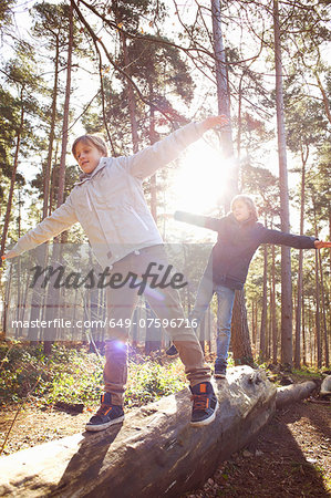 Twin brothers walking along fallen tree trunk in forest