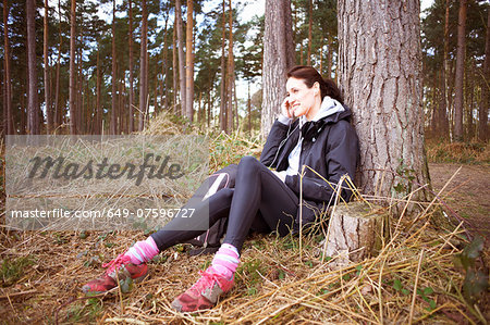 Mature woman runner talking on her cellphone in a forest Stock Photo - Premium Royalty-Free, Image code: 649-07596727