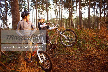 Twin brothers holding BMX bikes chatting in forest Stock Photo - Premium Royalty-Free, Image code: 649-07596733