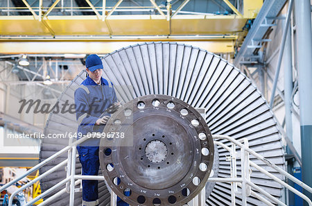 Engineer inspecting turbine in workshop Stock Photo - Premium Royalty-Free, Image code: 649-07596738
