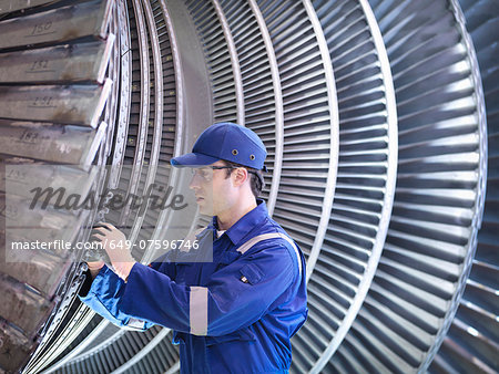 Engineer inspecting repair to steam turbine blade in workshop Stock Photo - Premium Royalty-Free, Image code: 649-07596746