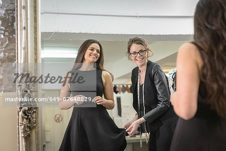 Fashion designers working together in front of mirror in fashion studio Stock Photo - Premium Royalty-Free, Image code: 649-07648029