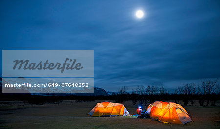 Mature woman sitting outside tent at night, Skaftafell, Vatnajokull National park, Iceland Stock Photo - Premium Royalty-Free, Image code: 649-07648252
