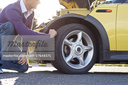 Man inspecting car tyre Stock Photo - Premium Royalty-Free, Image code: 649-07648371