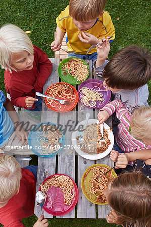 Overhead view of seven children eating spaghetti at picnic table Stock Photo - Premium Royalty-Free, Image code: 649-07648415