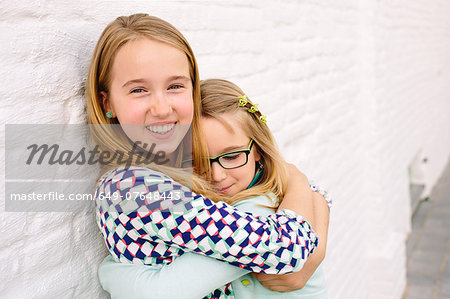Two sisters holding hugging next to white wall Stock Photo - Premium Royalty-Free, Image code: 649-07648443