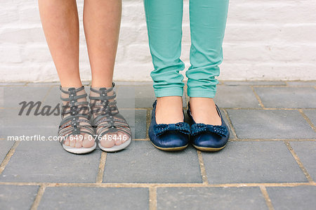 Close up of two sisters legs and footwear Stock Photo - Premium Royalty-Free, Image code: 649-07648446
