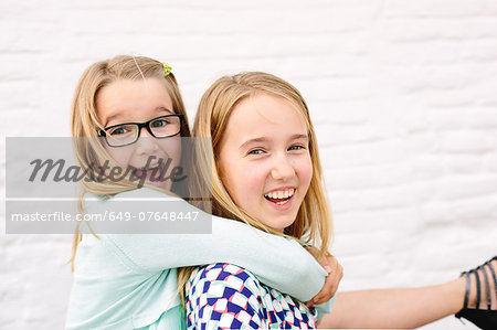Two sisters playing piggyback Stock Photo - Premium Royalty-Free, Image code: 649-07648447
