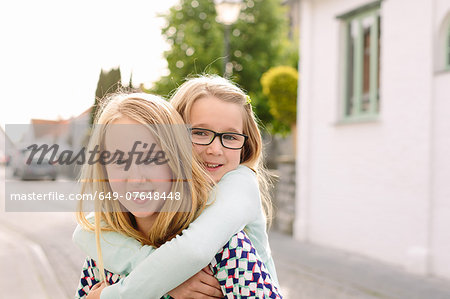 Portrait of two sisters playing piggyback Stock Photo - Premium Royalty-Free, Image code: 649-07648448