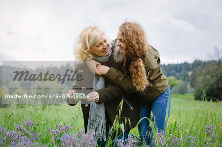 Teenage daughter and mother with smartphone