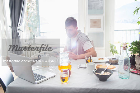 Young man having breakfast and using laptop Stock Photo - Premium Royalty-Free, Image code: 649-07648561
