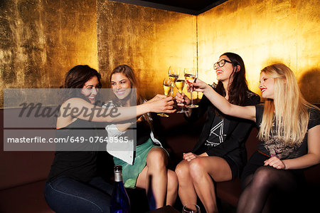 Four female friends toasting with wine in nightclub Stock Photo - Premium Royalty-Free, Image code: 649-07648585